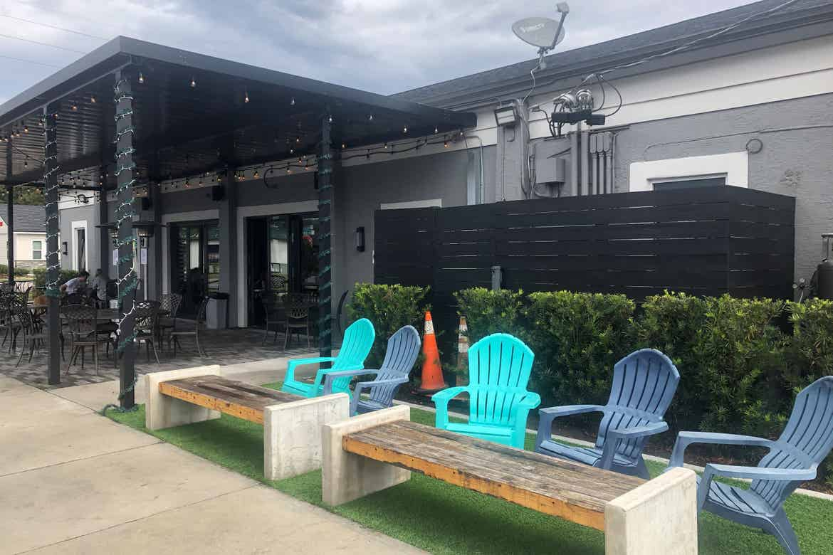 A covered patio exterior and multi-colored adarondak chairs outside of 'Hourglass Brewing.'