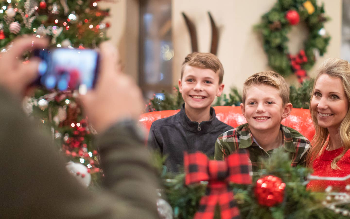 Author, Amanda Nall (left), pose on Santa's sleigh with her sons for a photograph surrounded by holiday decor.