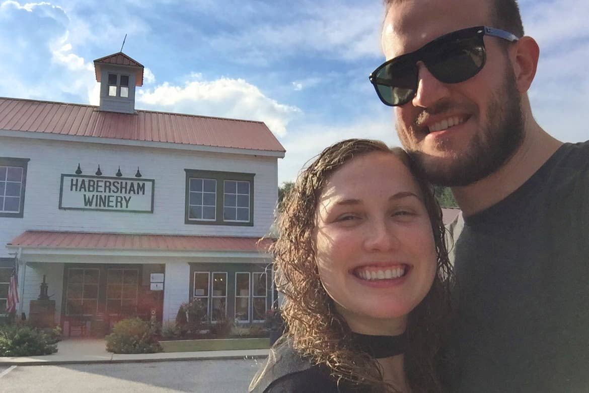 A caucasian man (right) and a caucasian woman (left)  stand in front of a white building with red tin roof with a sign that reads, ' Habersham Winery.'