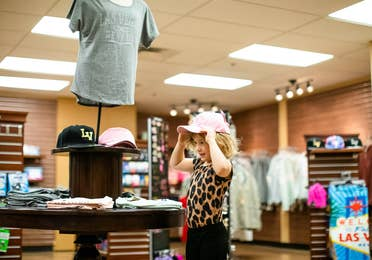 Young child trying on pink Las Vegas hat in the Marketplace at Desert Club Resort in Las Vegas, Nevada.