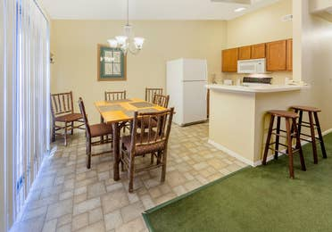 Kitchen and dining room table with five chairs in a two-bedroom cabin at Ozark Mountain Resort in Kimberling City, Missouri