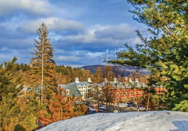 Oak n' Spruce Resort in South Lee, Massachusetts surrounded by fall foliage and some snow on the ground.