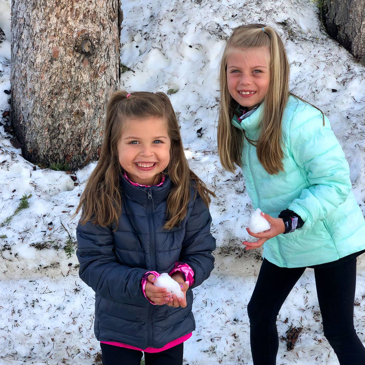 Author, Chris Johnstons' daughters, Kyndall (right), and Kyler (left) play in the snow at Mt. Washburn wearing winter coats.