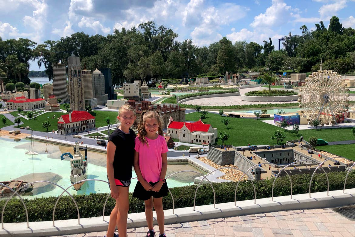 Two young girls stand in front of a scaled city made entirely of LEGOS.