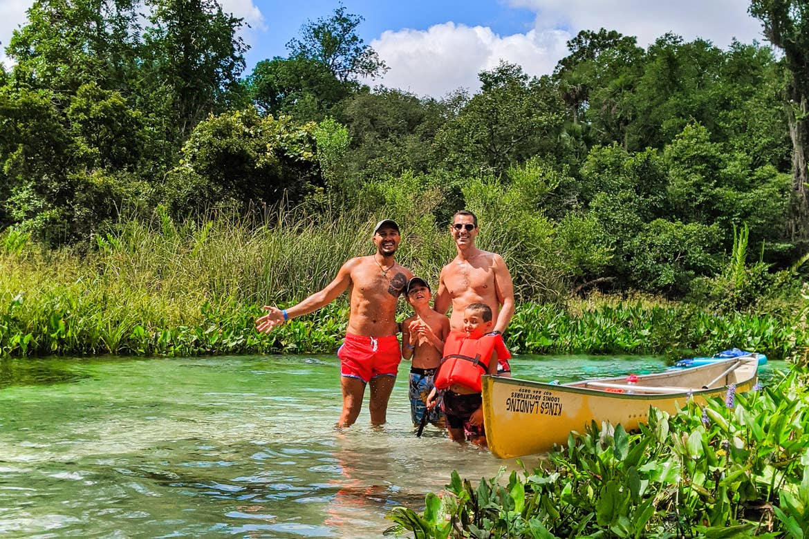 Two men (back left and back right) stand with two young boys (front left and right) wearing swim trunks next to a kayak in the waters of Wekiva River in Florida.