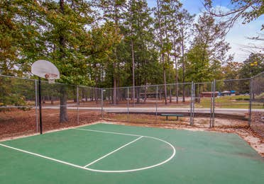 Outdoor basketball court with one hoop at Holly Lake Resort in Texas.