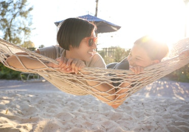Family enjoying hammock on the sand at Orange Lake Resort near Orlando, Florida
