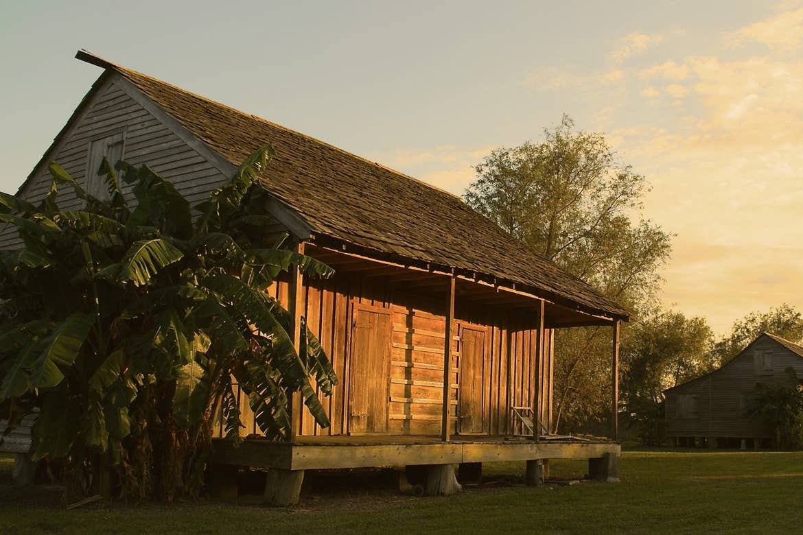 A retired wooden shack that once housed slaves at the Whitney Plantation stands vacant on a green field as the sun sets.