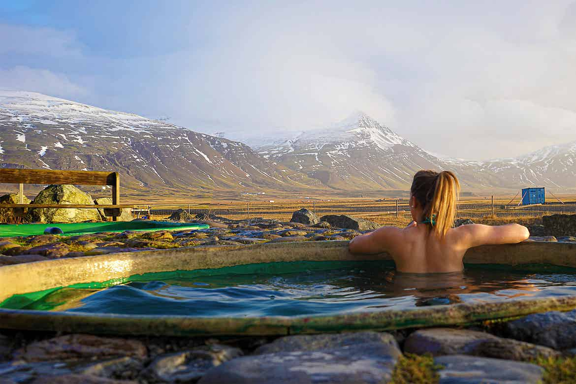 Featured Contributor, Ashlyn George, sits in a hot spring looking at the mountains of Iceland.
