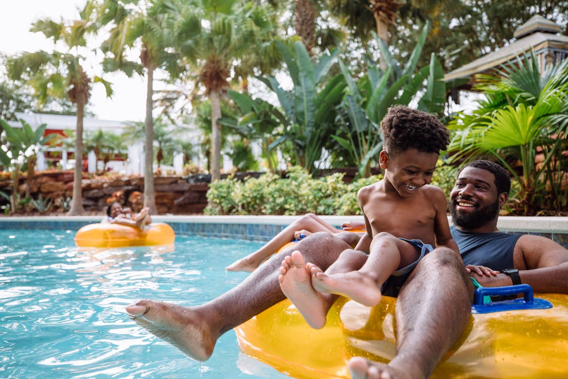 A man and young boy share an inner tube down a lazy river.