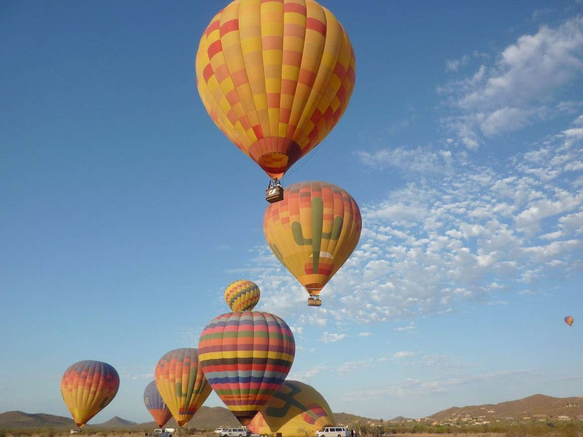 A few hot air balloons flying in the Arizona sky.