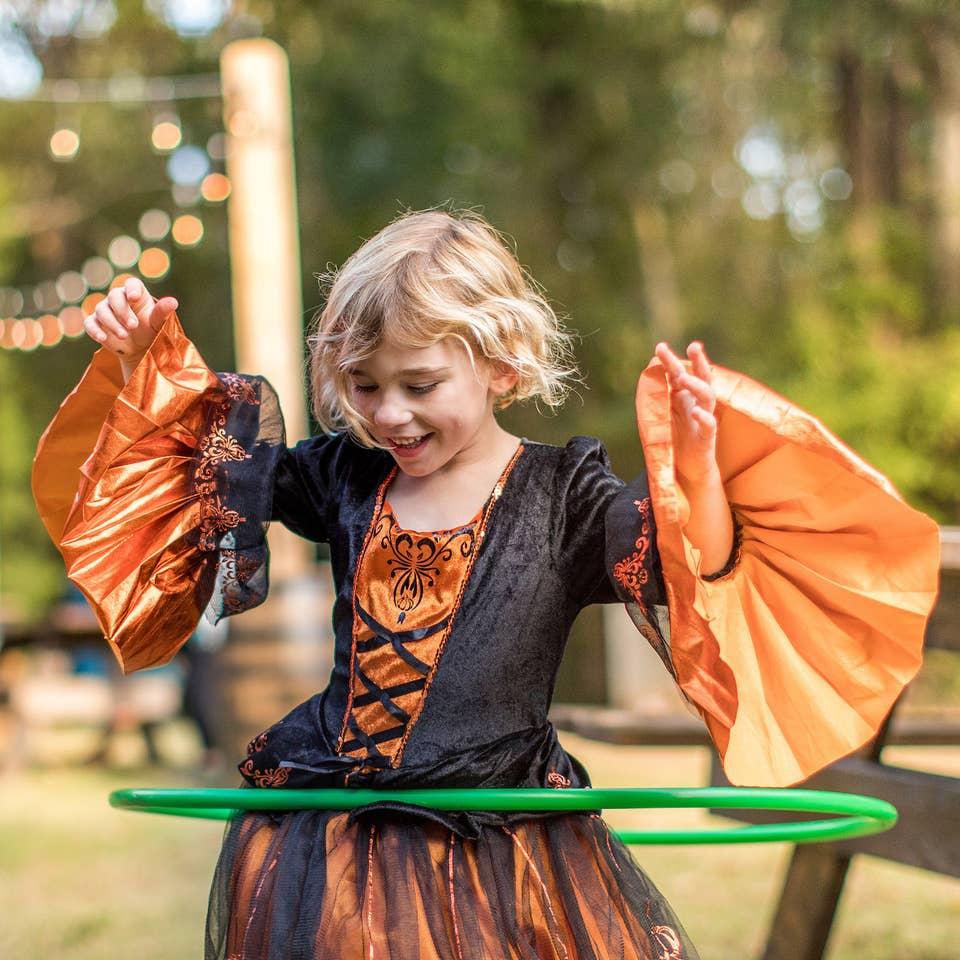 Child hula-hooping in a Halloween costume.