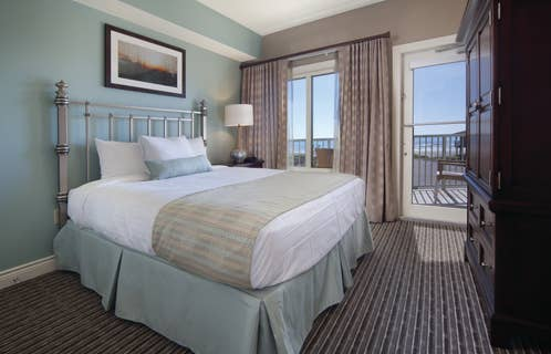 Master bedroom with access to furnished balcony in a two-bedroom villa at Galveston Beach Resort