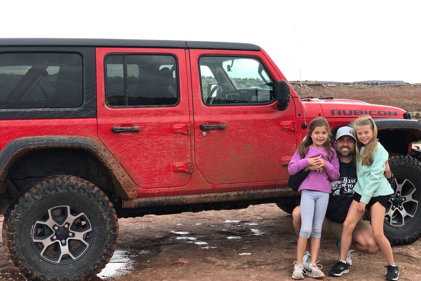 Josh (middle) and daughters (left and right) pose in front of their red Jeep Rubicon for some off-roading adventures.