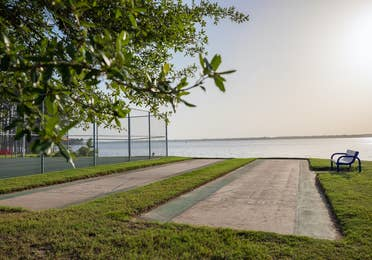 Outdoor shuffleboard court with view of lake at Villages Resort in Flint, Texas.
