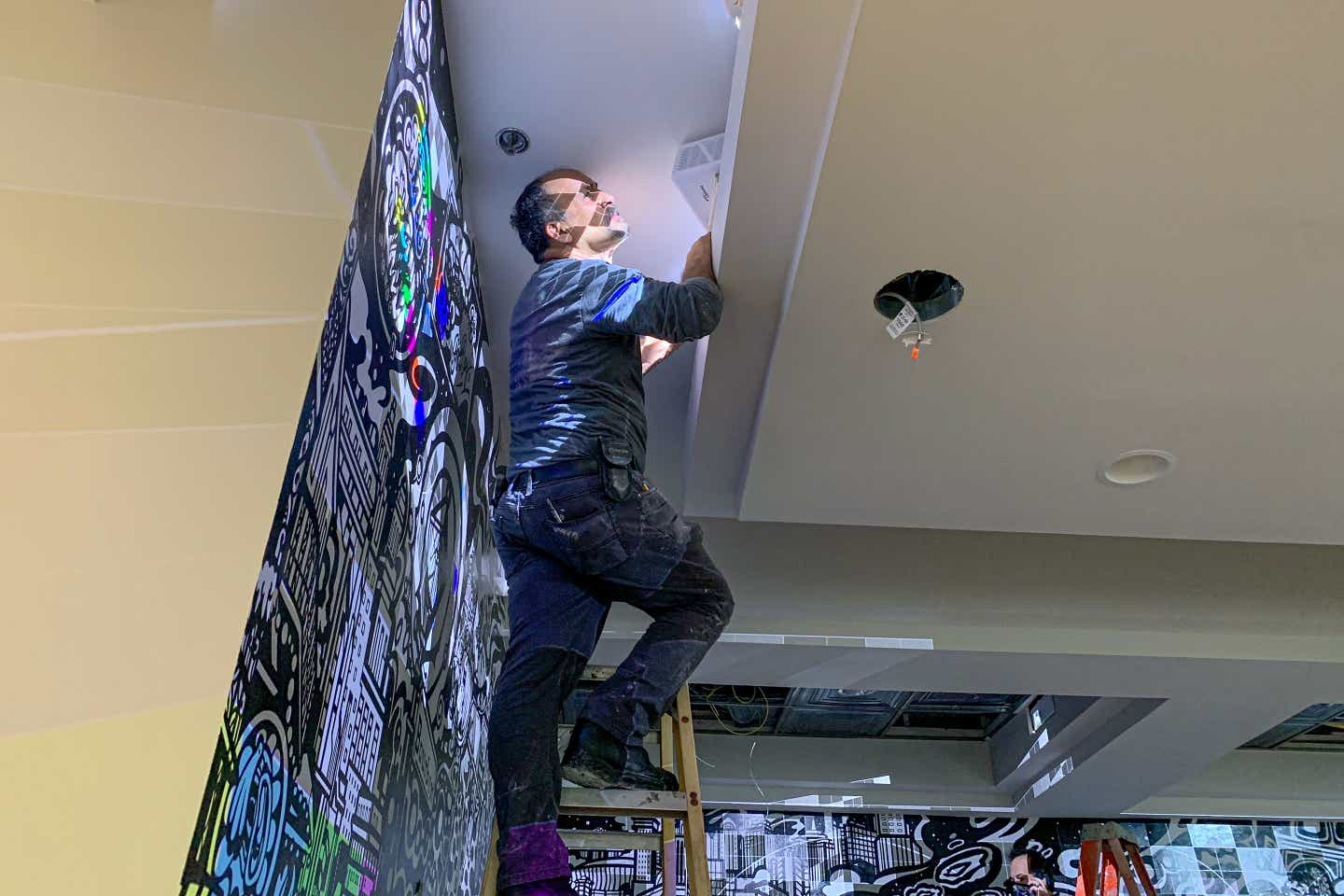 A man climbing a ladder while adjusting colored projectors for the outlined mural art featured in the lobby of our resort in New Orleans, Louisiana.
