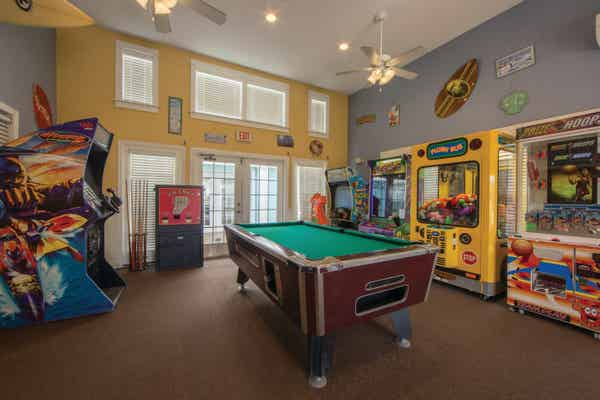 Arcade with a billiards table in the center of the room at Galveston Seaside Resort