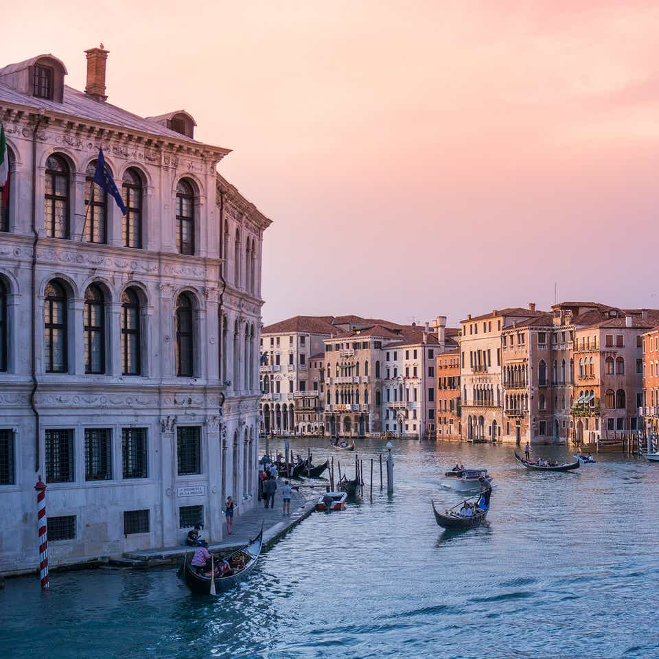 The rivers of Venice with gondolas and structures under sunset pink skies.