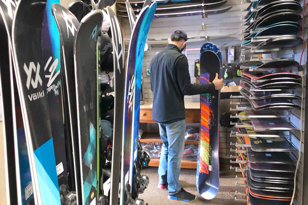 Team Member, 'Ernie', prepares to wax a snowboard in the Resort Sport Shop surrounded by various snowboards.