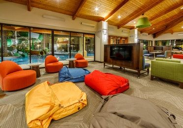 Comfortable seating in front of a television and large windows that look onto the pool area