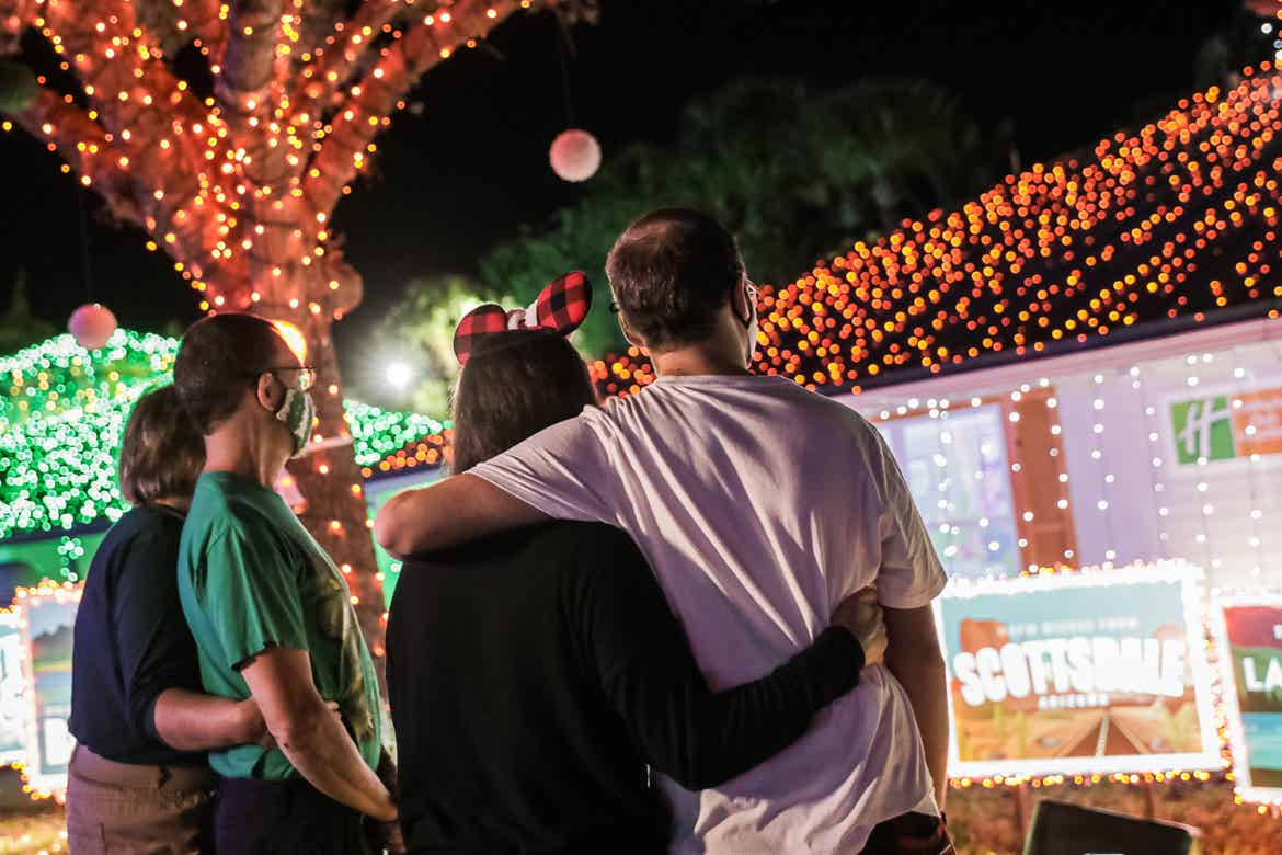 Kyle Bergen (right) and family wear their masks as they look at the exterior Villa decorations with colored string lights and giant postcard designs.
