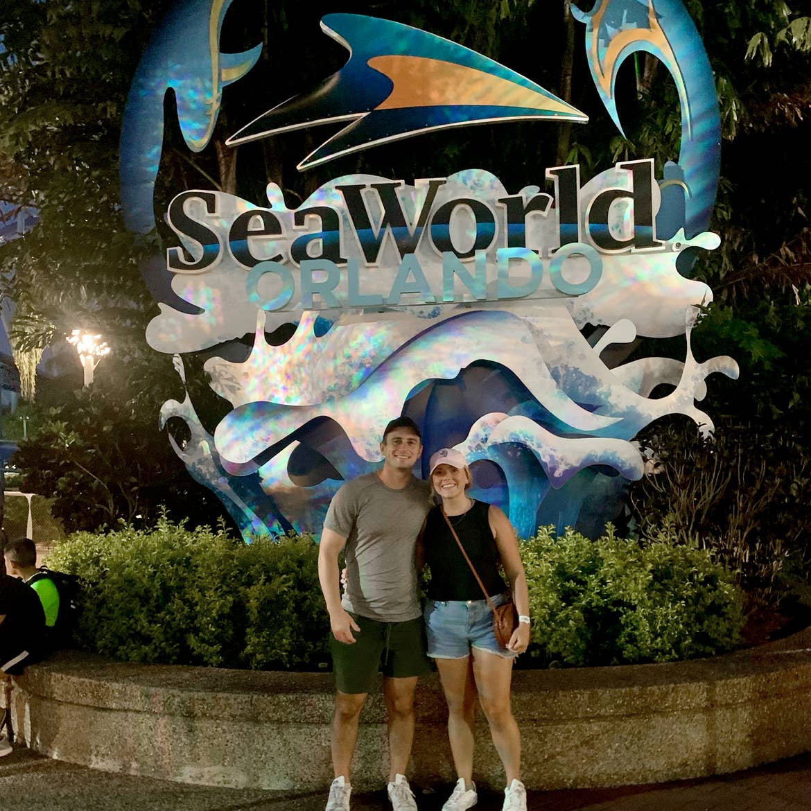 A Caucasian male wearing a grey t-shirt, black cap (right) and a Caucasian female wearing a pink baseball cap and black tank top stand near the SeaWorld Orlando sign icon.
