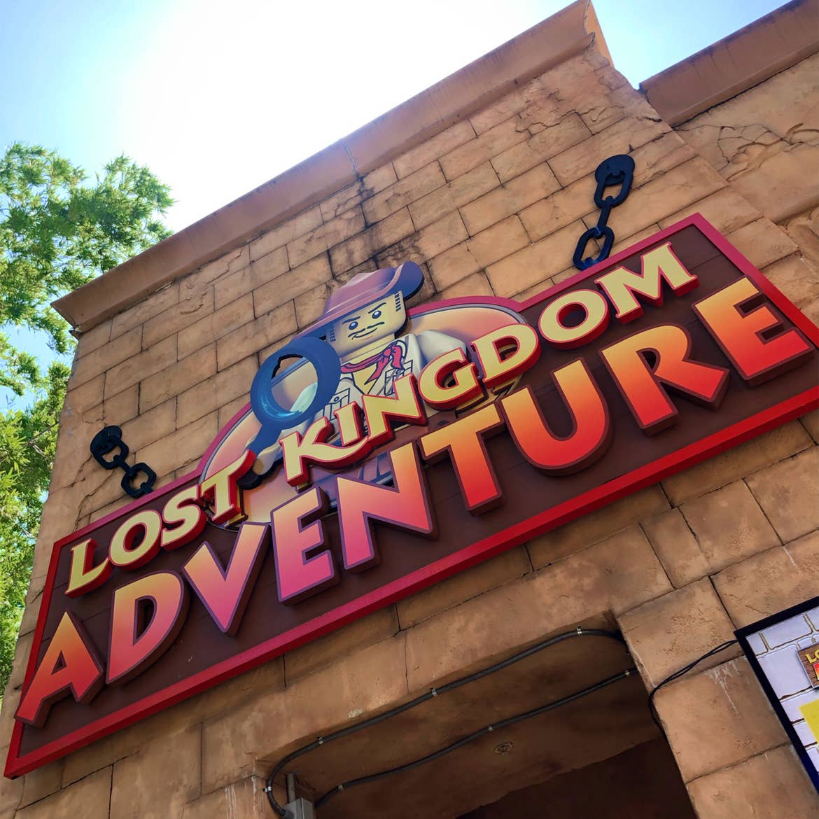 The exterior of an attraction made of brick with a marquee that reads, 'Lost Kingdom Adventure.'