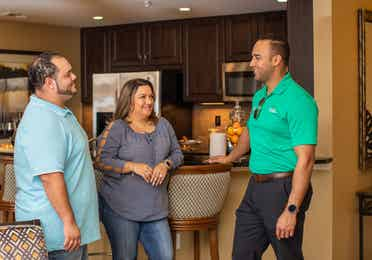 A couple standing with a salesman in a villa located at Orange Lake Resort in Orlando, FL