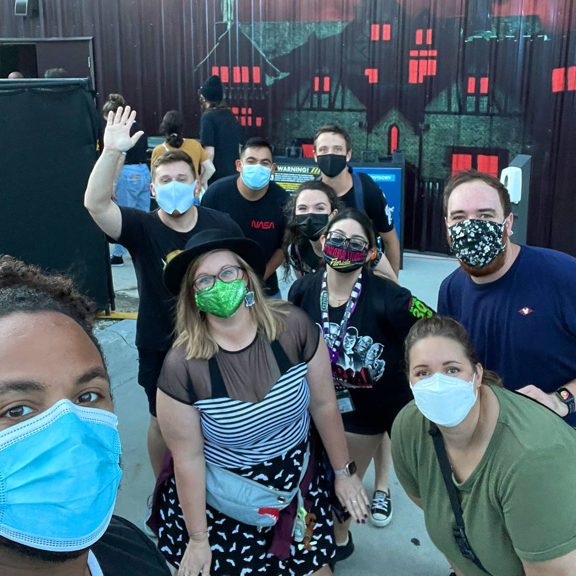 A group of men and women wear safety masks outside of a haunted house.