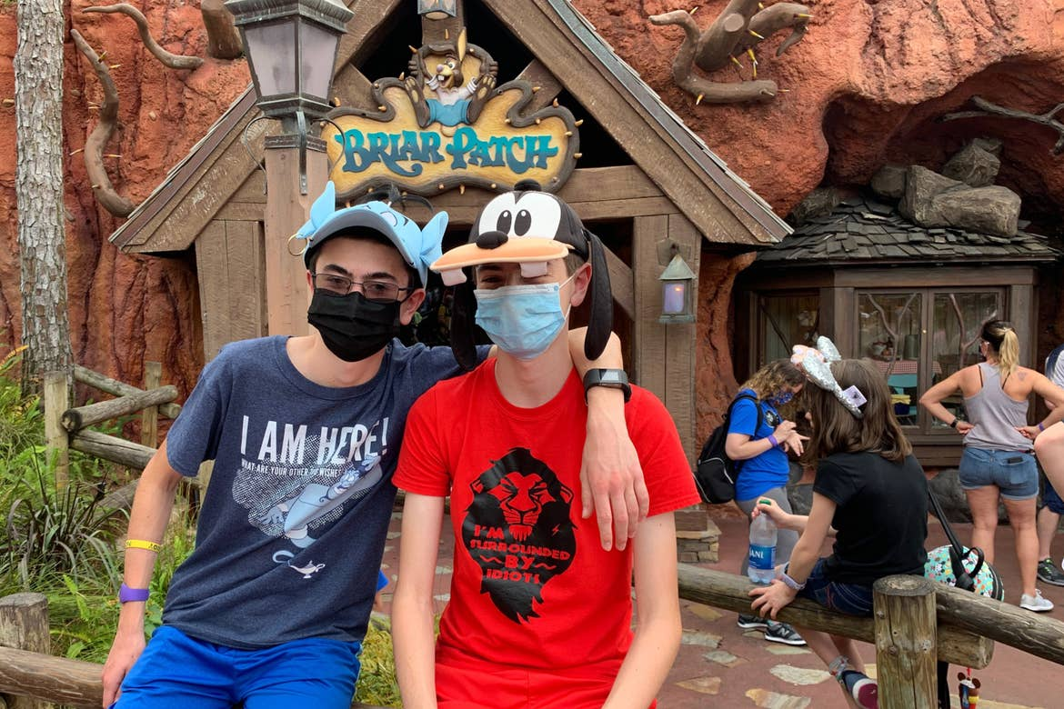Two boys sit in front of the 'Briar Patch' shop near Splash Mountain in Magic Kingdom at Walt Disney World Resort wearing a Genie hat and shirt (left) and a Goofy hat and Scar shirt (right).