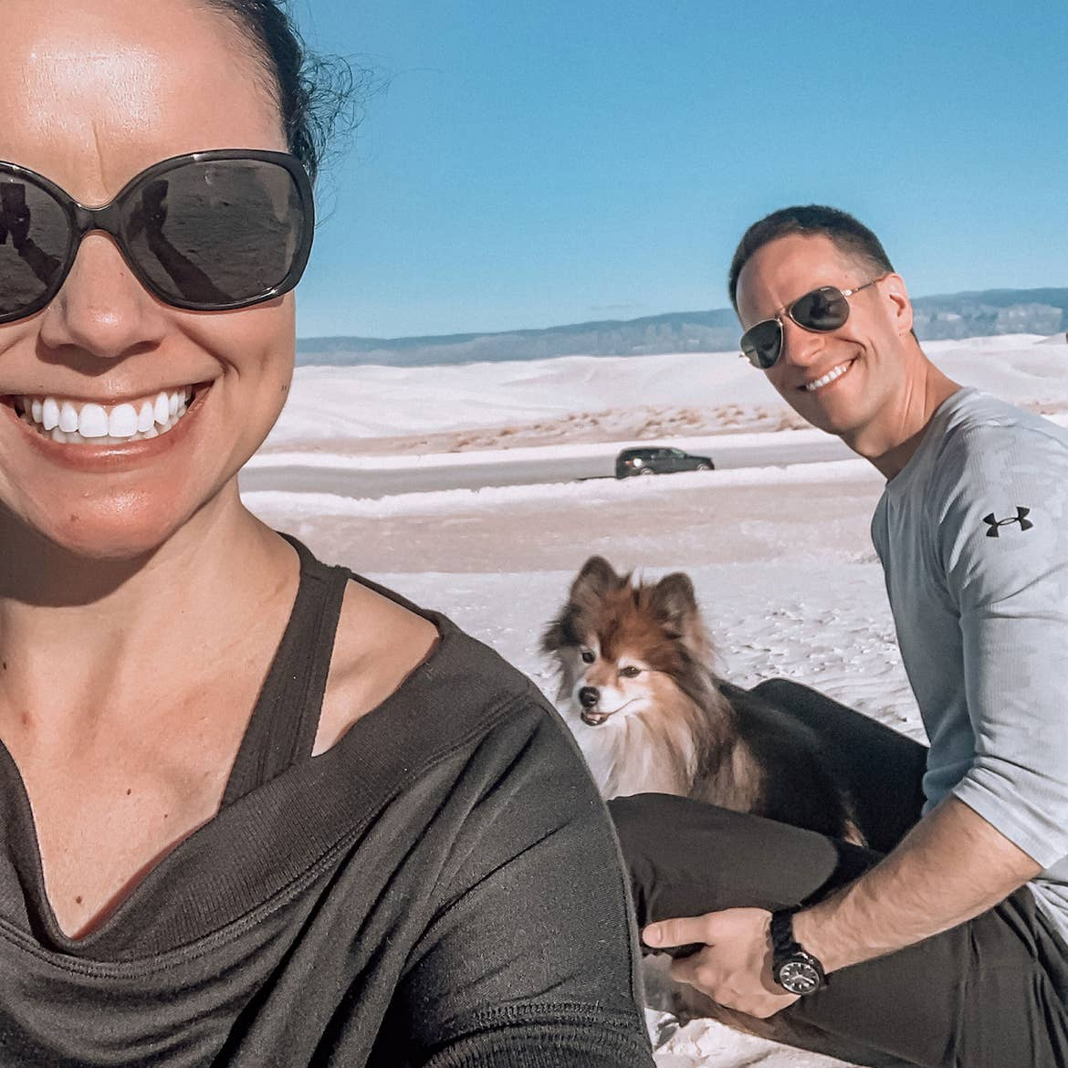 Authors, Lauren Layne and Anthony LeDonne, sit in front of their vehicle with Bailey the Pomeranian at the White Sands National Monument.