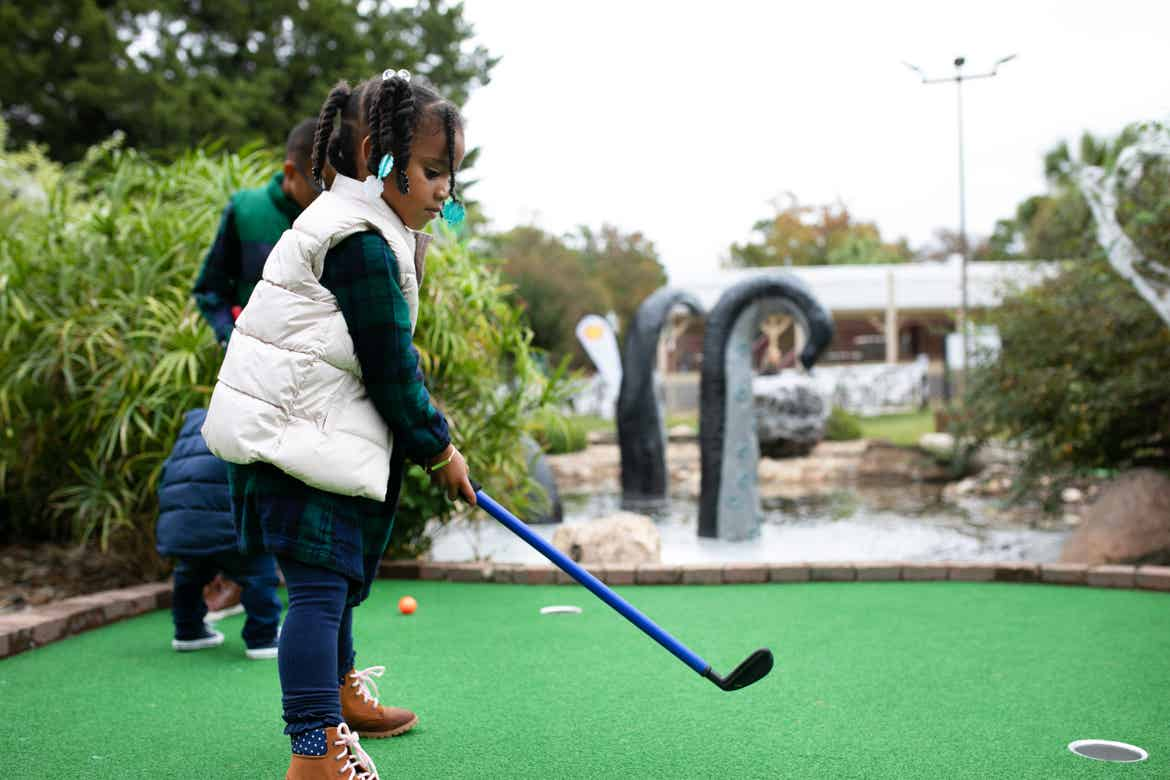 Tina's daughter getting ready to hit her golf ball during spooky mini golf at Falladays at Villages Resort.