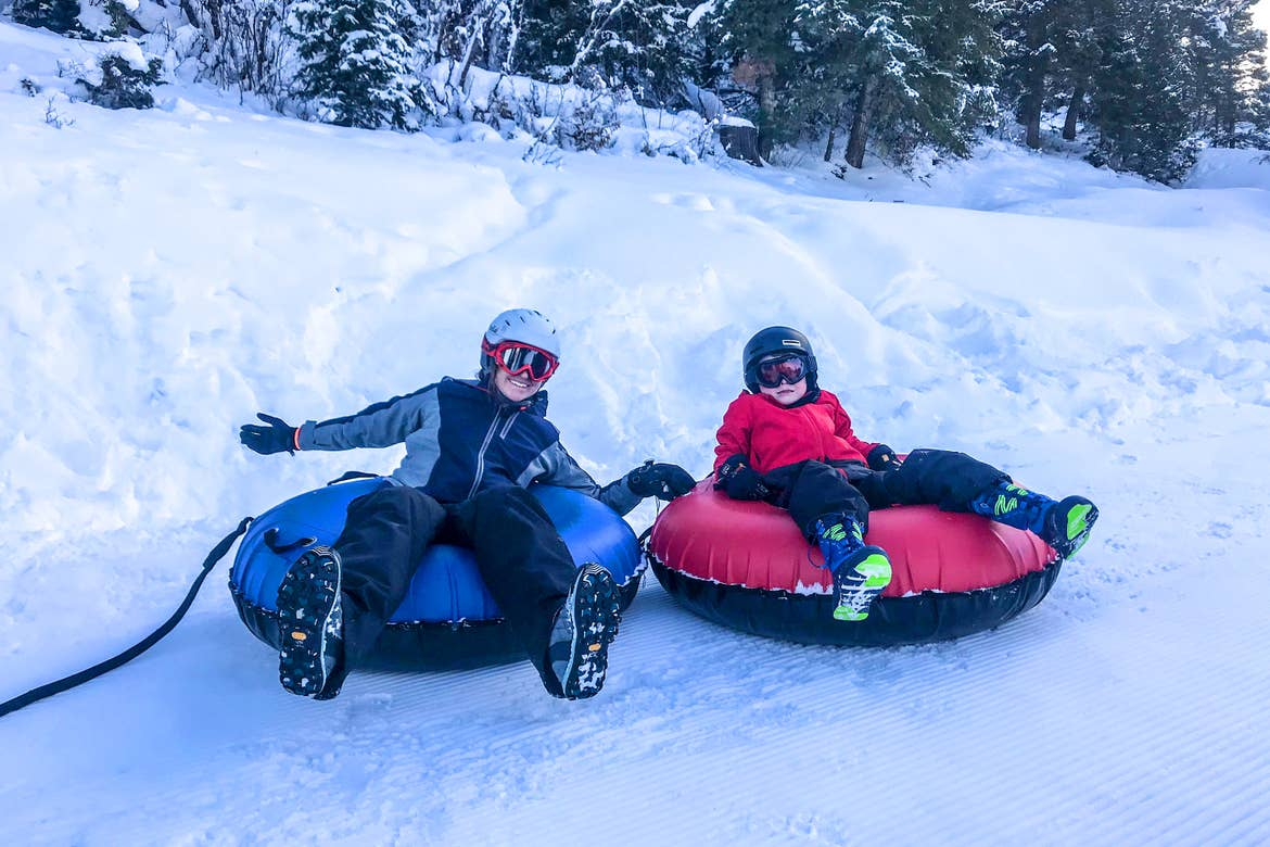 Featured Contributor, Jessica Averett (left), wears a winter jacket and snow pants, red goggles, and white helmet on a blue inner tube next to her son (right) wearing a red winter jacket, black snow pants, and black goggles and helmet on a red innertube.