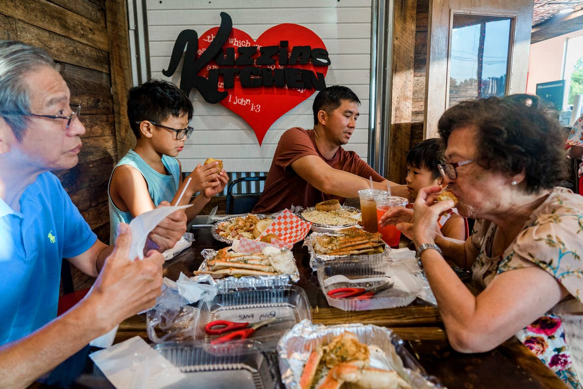 A multi-generational Asian family enjoys various food near a shiplapped wall with a heart-shaped marquee that reads 'Kuzzin's Kitchen'