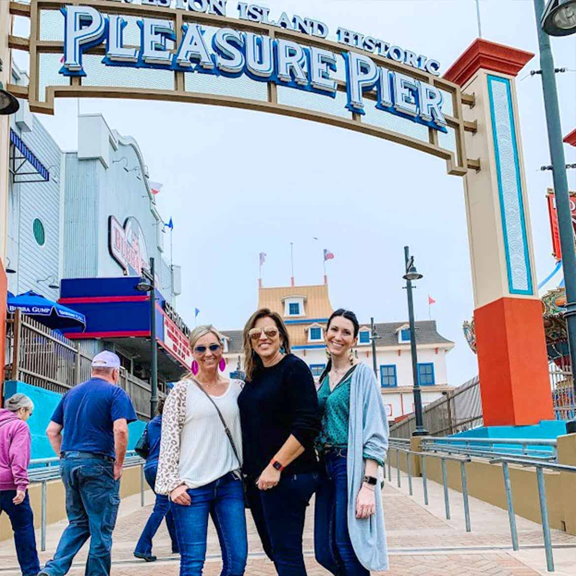 Featured Contributor, Amanda Nall (left) poses with her two friends in front of the Paradise Pier in Galveston, Tx.