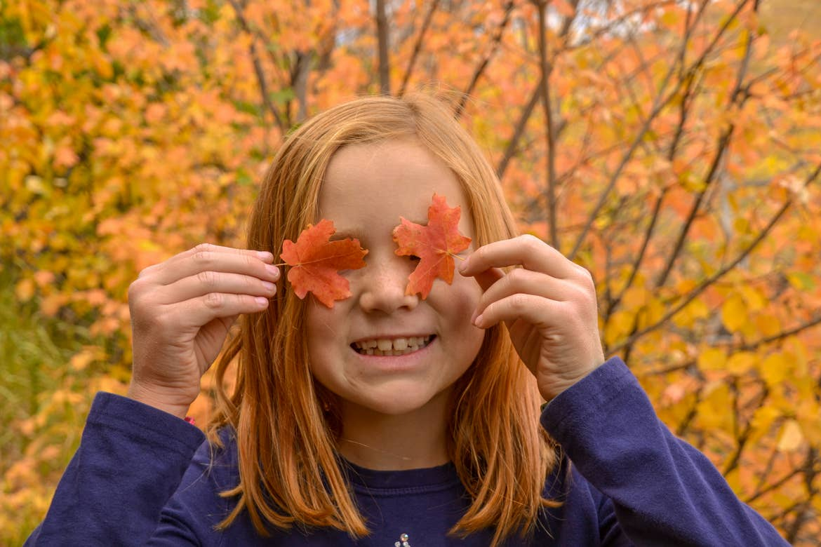 Jessica's daughter covering her eyes with small orange leaves