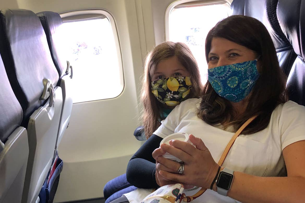 Chris (right) with daughter (left) wearing masks while on an Airplane for safety.