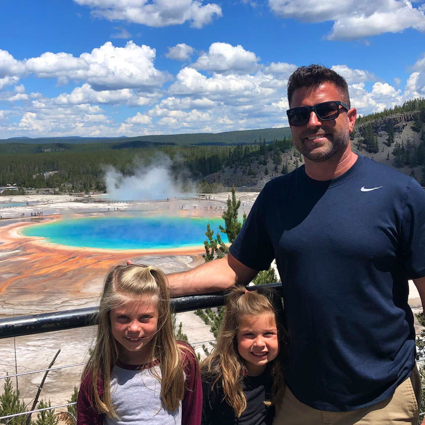 Author, Chris Johnstons' husband, Josh (far-left), stands in front of the Grand Prismatic Springs Springs at Yellowstone National Park with their daughters, Kyndall (front-left), and Kyler (front-right).