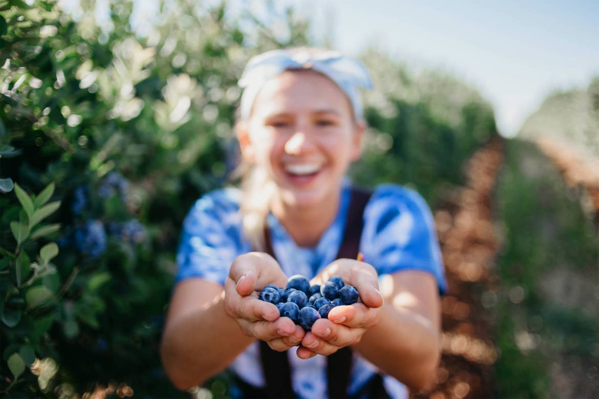 A woman holds a bunch of blueberries in hand outdoors.