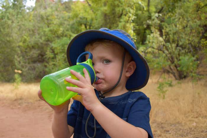 The youngest Averett stays hydrated and dressed to beat the desert heat with a blue sunhat and green water bottle.