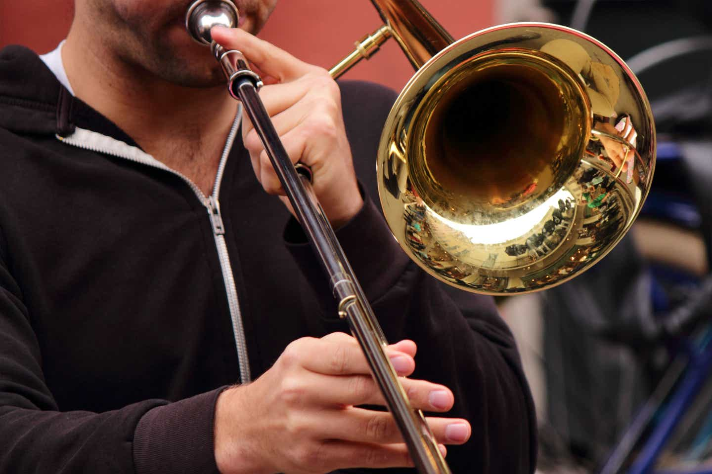 Jazz performer wearing a black zip-up hoodie plays a gold trombone on the streets of New Orleans.