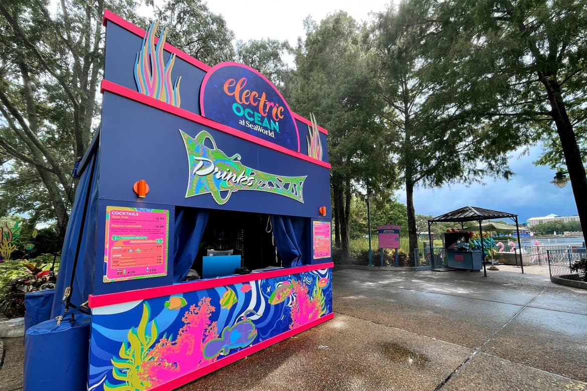 An Electric Ocean vendor kiosk decorated in neon colors stands on concrete pavement in SeaWorld Orlando.