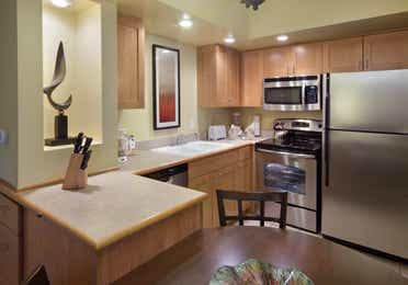 Kitchen with stainless steel fridge, microwave, sink, oven, and dishwasher in a one-bedroom villa at Lake Geneva Resort