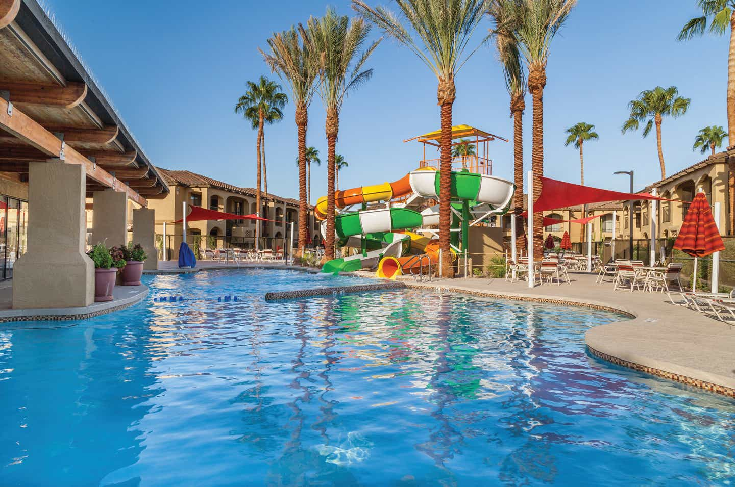 Swimming pool with tables and chairs and a large water slide at Scottsdale Resort in Arizona