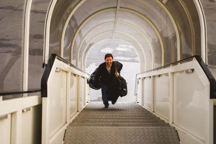 Sara's husband is running up a covered staircase at the airport carrying his luggage and smiling.