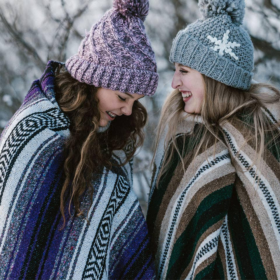 Two girls outside in the snow wearing blankets and beanies while laughing.