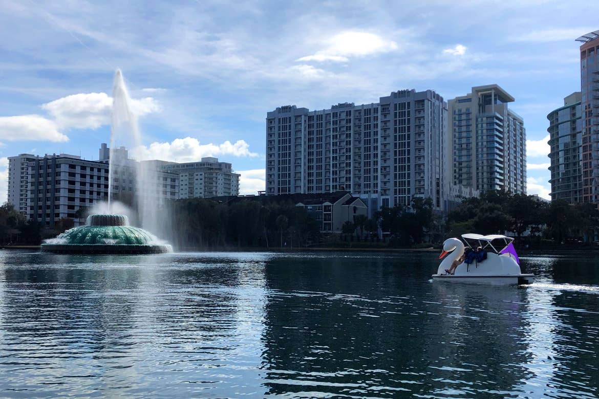 A woman paddles a white Swan boat in Lake Eola under a blue sky.