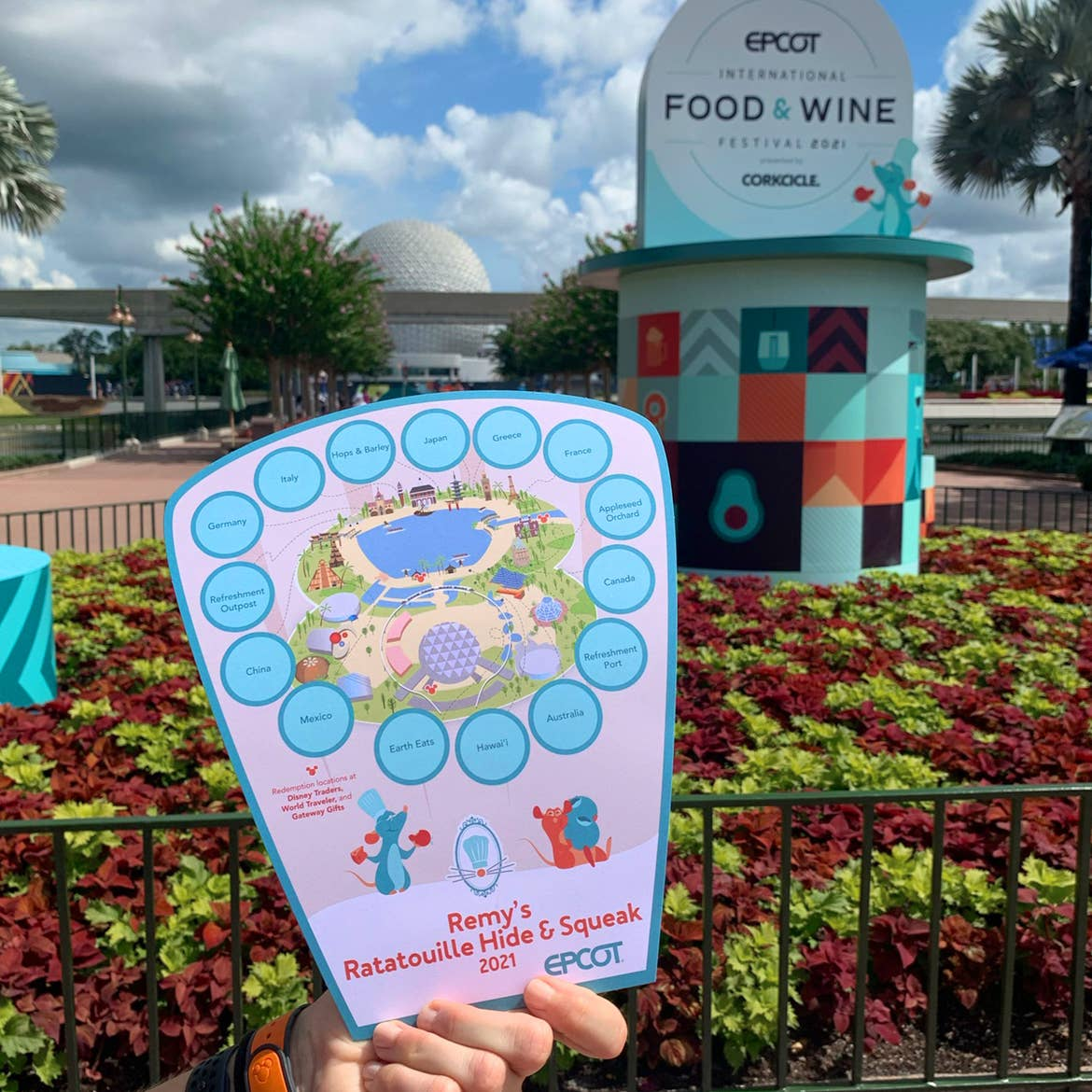 A hand holds a map for 'Remy's Hide & Squeak Scavenger Hunt' near a garden display sign with the Epcot Geosphere in the background.