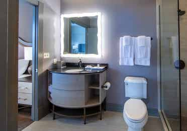 Bathroom attached to bedroom with toilet, walk-in shower and sink with lighted mirror at New Orleans Resort in Louisiana.