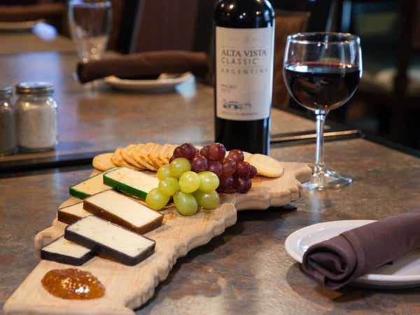 Cheese plate with cheeses, grapes and red wine.
